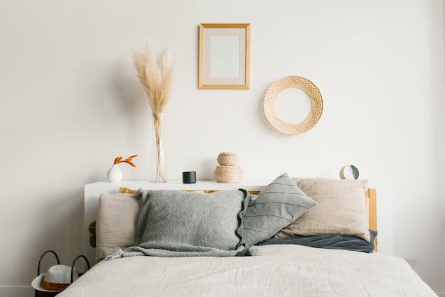 北欧のシンプルなナチュラルスタイルのベッドルーム。ベッドの上の灰色の枕。ベッドの上の装飾