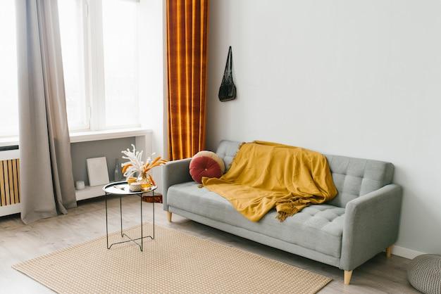 スカンジナビアのシンプルな自然なスタイルのリビングルームのグレーのソファー、黄色と赤の色彩