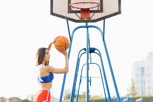Красивая спортивная стройная девушка держит баскетбольный мяч летом на спортивной площадке