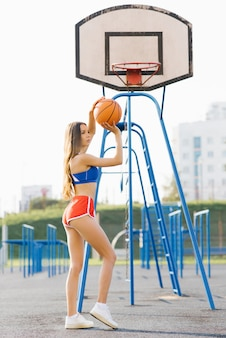 Красивая спортивная стройная девушка в коротких шортах держит баскетбольный мяч летом на спортивной площадке