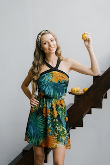 プロのメイクと新鮮な有機レモンを保持しているサンドレスでカールを持つスタイリッシュな美しい少女