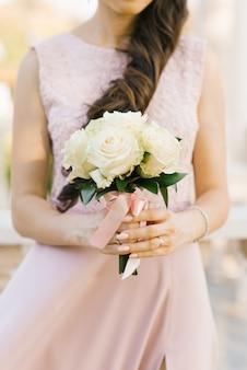 ピンクのドレスの少女の手に白いバラの美しい花束