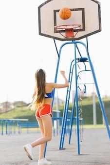 Красивая стройная спортивная девушка летом играет в баскетбол на детской площадке в шортах и топе