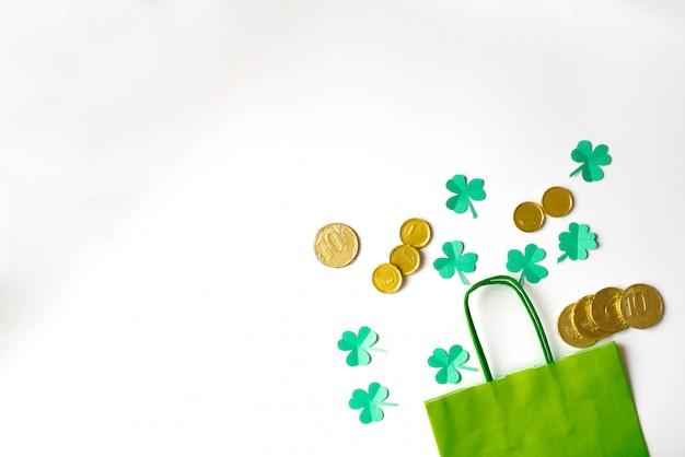 聖パトリックの日の割引。白地に金貨と緑の紙袋と紙のクローバーの葉。