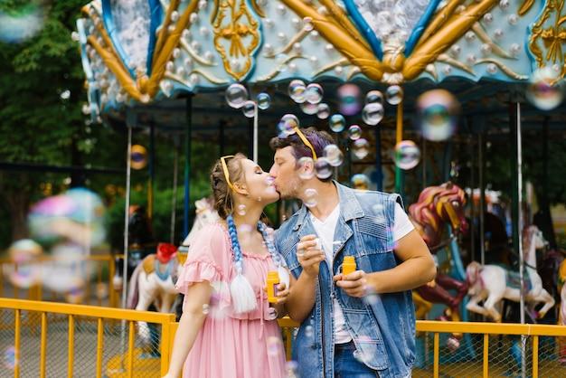 Красивые яркие веселые романтичные влюбленные пары наслаждаются мыльными пузырями в парке развлечений и целуются
