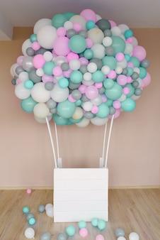 ピンク、グレー、ホワイト、ミントの風船で作られたフォトゾーンとホリデーバルーンの装飾