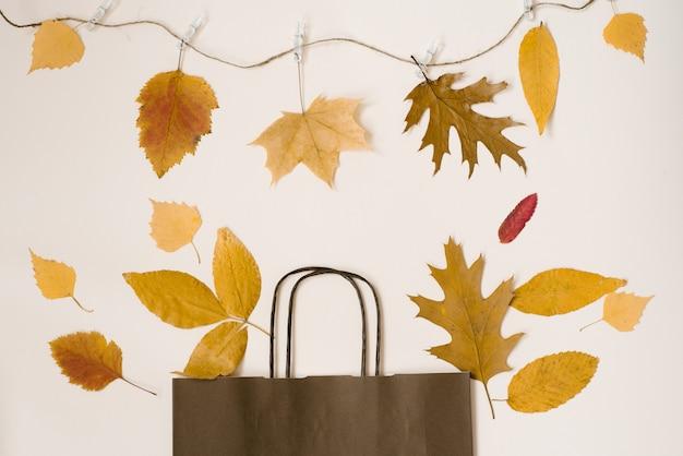 Яркий букет из осенних опавших листьев в подарок коричневой бумажной сумке. сезонная осенняя распродажа. цены падают