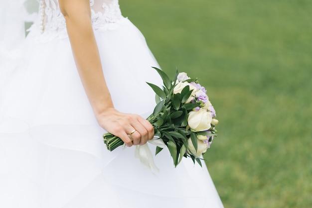 Красивый нежный свадебный букет невесты с лиловой эустомой и кремовыми розами в руках невесты