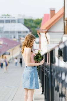 女の子は街の歴史的な部分の通りを歩き、フェンスの近くに立って彼を抱きしめます