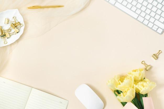 様式化された女性のデスク、オフィスデスク。コンピューター、黄色いチューリップの花束、クリップボードのあるワークスペース。ライトベージュの背景の女性のファッションアクセサリー。フラットトップビュー