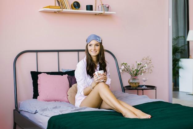 Милая красивая брюнетка в розовом халате сидит на кровати в розовой спальне, утром держит чашку чая или кофе и улыбается