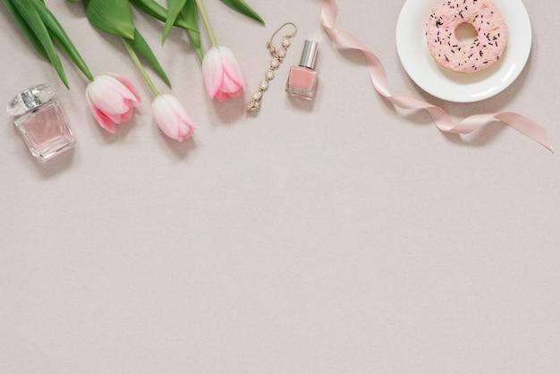 ブログの春のコンセプトバナー。ピンクのチューリップ、マニキュア、オードトワレ、コピースペースとほこりっぽいベージュ色の背景のブレスレット。ファッションブログ