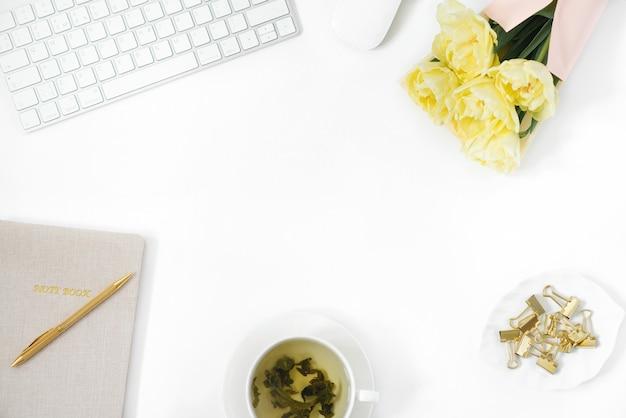 様式化された女性のホームオフィスデスク。コンピューター、チューリップの花束、白いプレートに金色のクリップ、メモ帳、孤立した白い壁に金色のペンがあるワークスペース。フラット横たわっていた。上面図。