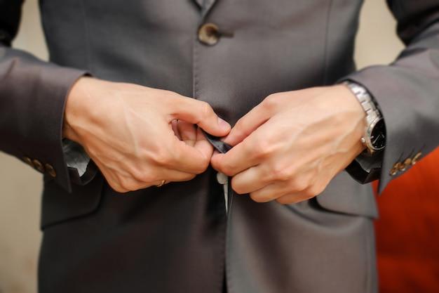 灰色のジャケットにボタンを留める男性