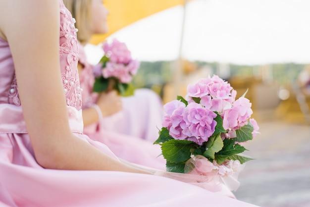 女の子の手にピンクのアジサイのブライドメイドの花束
