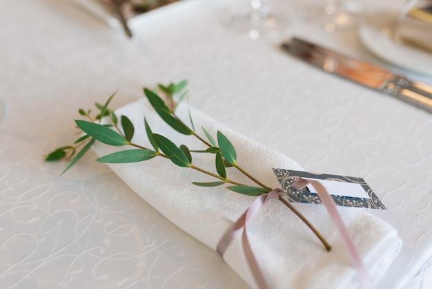 ユーカリの枝とほこりの多いピンクのリボンで結ばれた白いダイニングナプキン