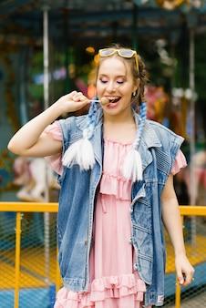 明るく陽気な女の子が棒でロリポップを食べて元気に笑顔