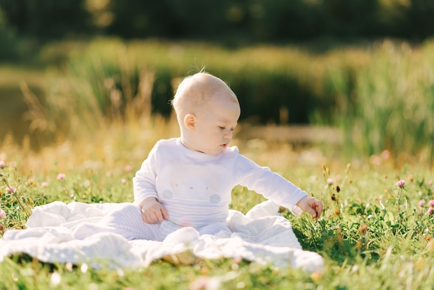 小さな子供は、戸外で湖の岸の毛布に座っています。赤ちゃんと一緒に夏の散歩