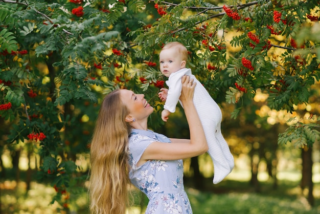 Молодая счастливая мать поднимает своего маленького сына на руках у рябины с красными ягодами летом в парке или саду и целует ее мальчика. день матери