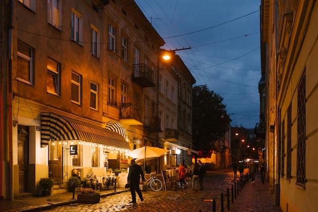 Львов, украина. туристы гуляют по вечернему старому городу
