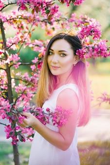 Красивая девушка с длинными прямыми волосами и большими глазами стоит в цветах розовой яблони. профессиональный макияж