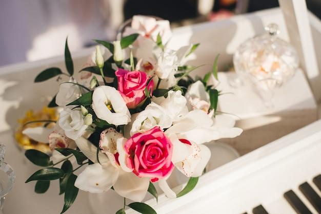 白いトルコギキョウ、蘭、ピンクのバラのウェディングフラワーアレンジメント