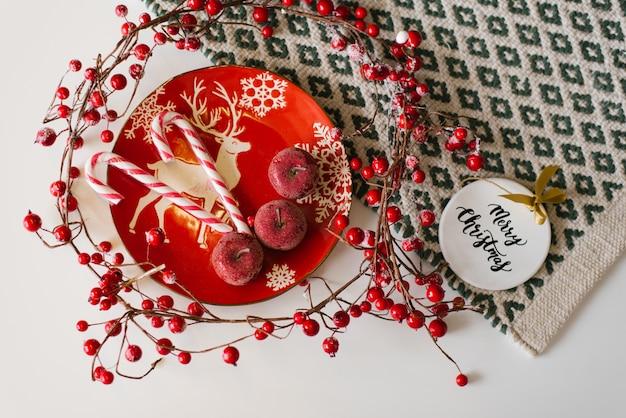 鹿と赤いクリスマスプレートに赤い果実とクリスマスグッズと嘘のラインの近くに赤い砂糖漬けリンゴとキャンディー杖