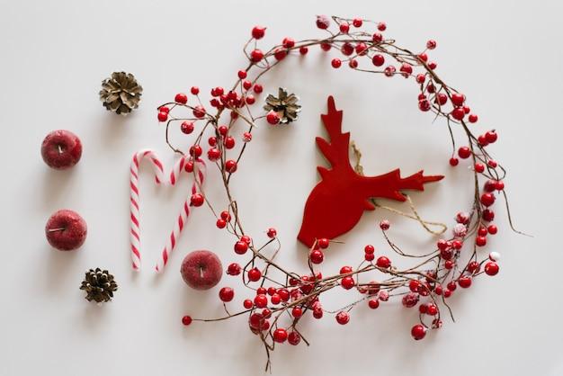 Красная рождественская елка игрушка голова оленя в окружении веточек с красными ягодами, шишки, красные яблоки и конфета на белом фоне. рождественская или новогодняя открытка