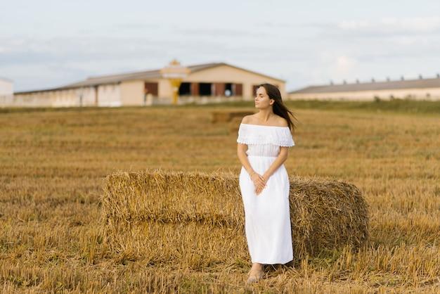 白いドレスを着た少女は、フィールドでわらのスタックの近くに立っています。