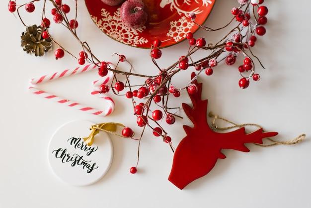 Рождественская и новогодняя открытка в красном и белом цвете. елочные украшения, красные ягоды и конфеты
