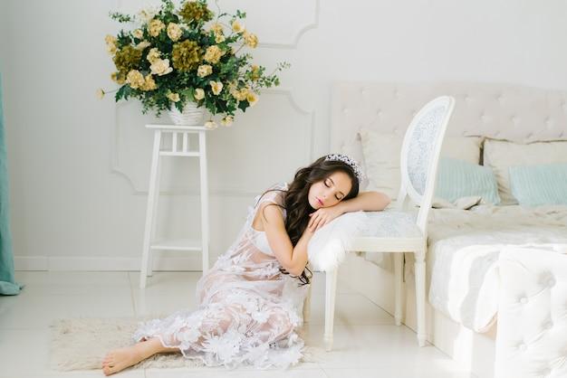 屋内で裸足で床に座って美しい白に乗る