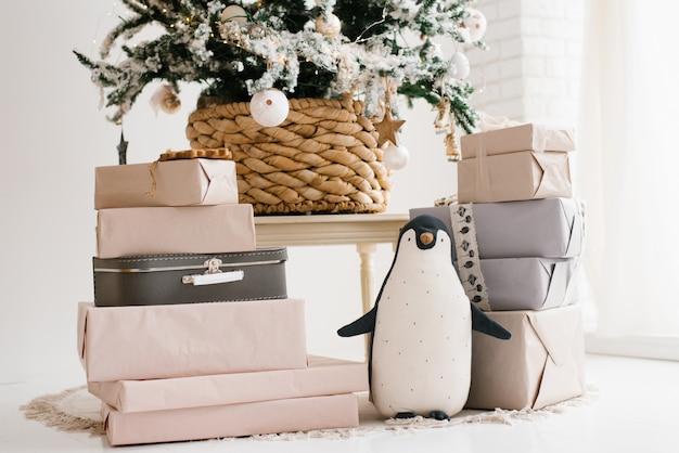 Новогодние подарки и мягкая игрушка пингвин под елкой
