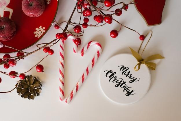 クリスマスカード、新年フラットレイアウト。クリスマスツリー、キャンディー、枝に赤い果実のおもちゃ