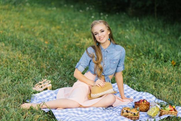 Милая усмехаясь молодая девушка сидя на одеяле. и он держит шляпу на летнем пикнике