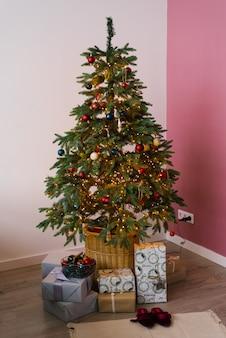 ピンクとピンクのリビングルームでクリスマスと新年のツリーの下に贈り物で飾られました。