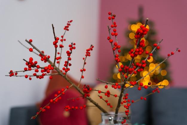 Ветки с ярко-красными ягодами на фоне рождественских новогодних огней