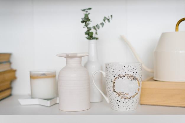 白とベージュ色のリビングルームの棚にマグカップ、花瓶、キャンドル