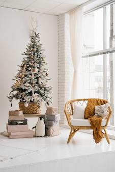 明るい色のリビングルームのクリスマスツリー、床から天井までの窓の近くの円形建築の椅子