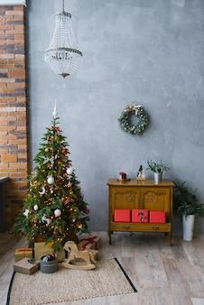 その下にライトとギフトが付いたクリスマスツリーは、家やアパートのリビングルームでキャッチのスタイルでリビングルームを飾る