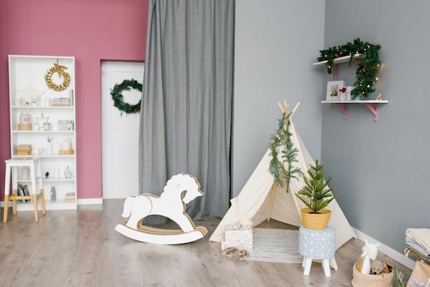 Детская комната, украшенная на рождество на розовом и сером