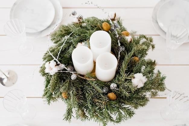 Елочный венок с белыми свечами, лежащими на столе, рождественский декор в светлых тонах