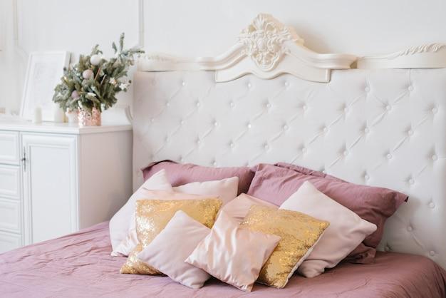 クリスマスに装飾された寝室の大きなダブルベッドにあるピンクとゴールドの枕