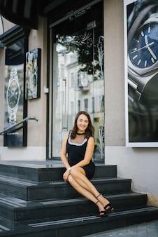 Зрелая элегантная женщина средних лет в платье сидит на черных гранитных ступеньках и улыбается