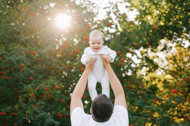 父親が幼い息子を抱きかかえ、彼は彼に微笑みかけます。