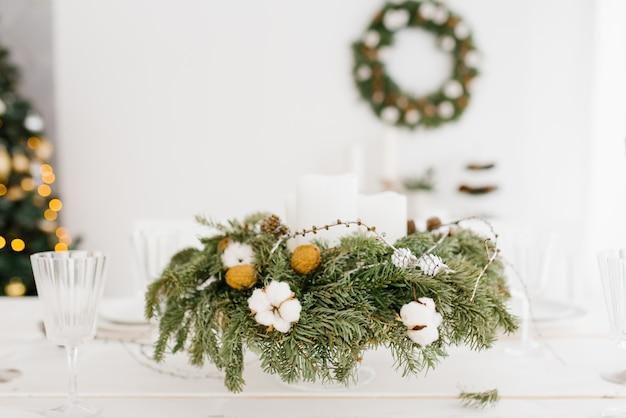 Новогодняя композиция из ели, хлопка, грецкого ореха на праздничном столе