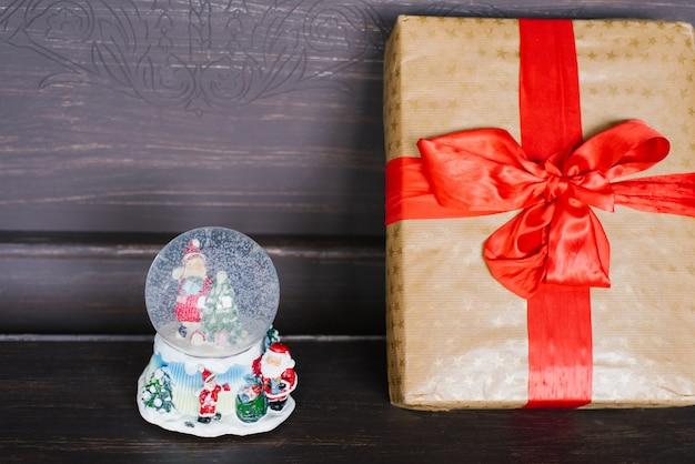 Сувенирный стеклянный новогодний снежный шар и подарок, завернутый в крафт-бумагу с красной лентой и бантом