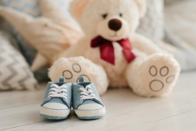 柔らかいおもちゃのクマの背景に赤ちゃんのための青いスニーカークローズアップ