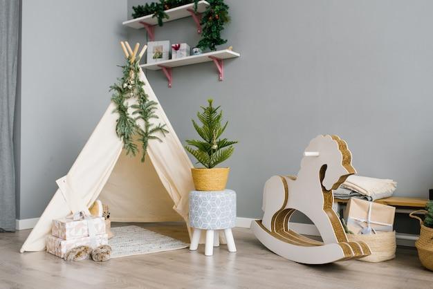 おもちゃ、ウィグワム、馬のある子供部屋。クリスマスの装飾