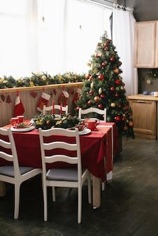 Традиционная столовая, украшенная к рождеству и новому году, ели с красными и золотыми елочными игрушками, столом и стульями. обеденный стол