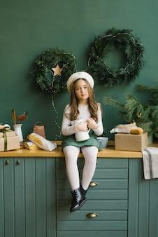 彼女の手で白い水差しを保持している素敵な女の子とスタイリッシュなキッチンに座っています。